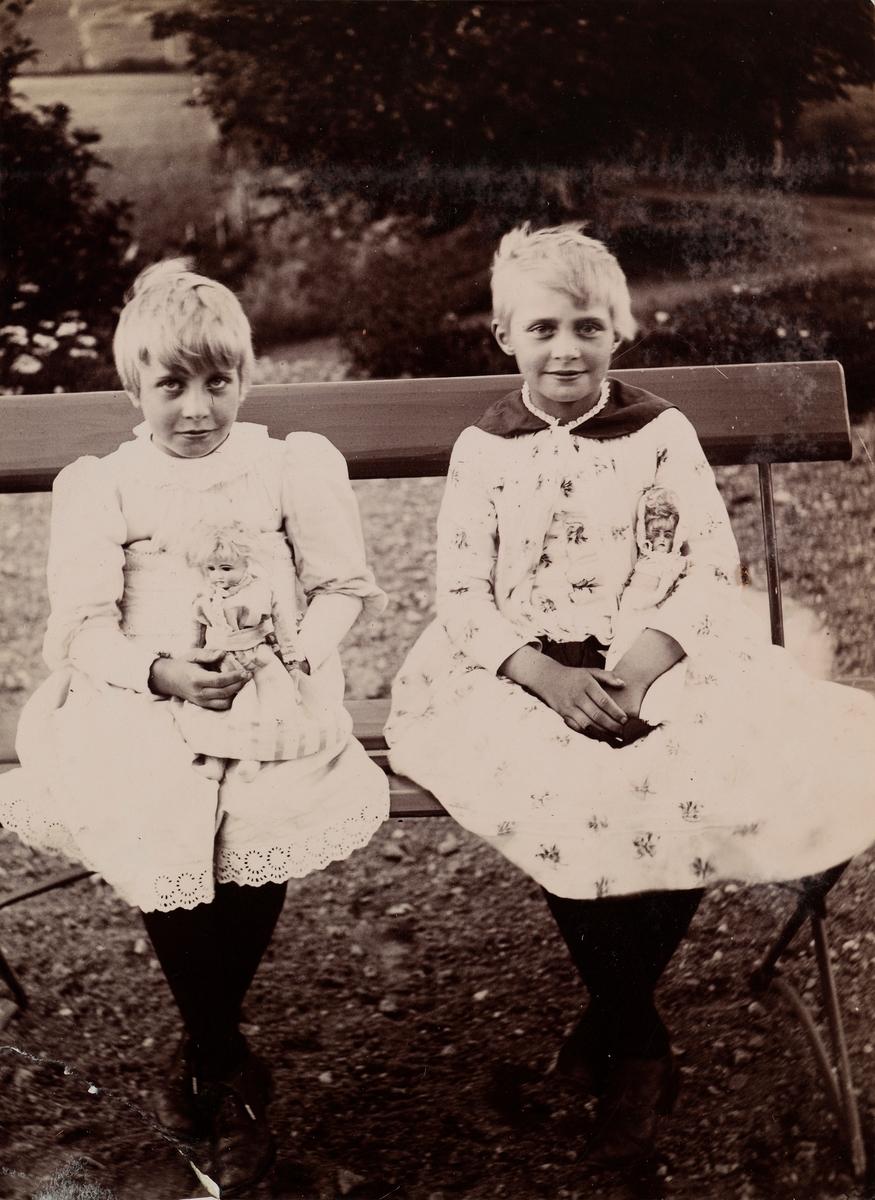 Eva og Minnie (Emilie) Christensen sitter på en benk med hver sin dukke i armen.