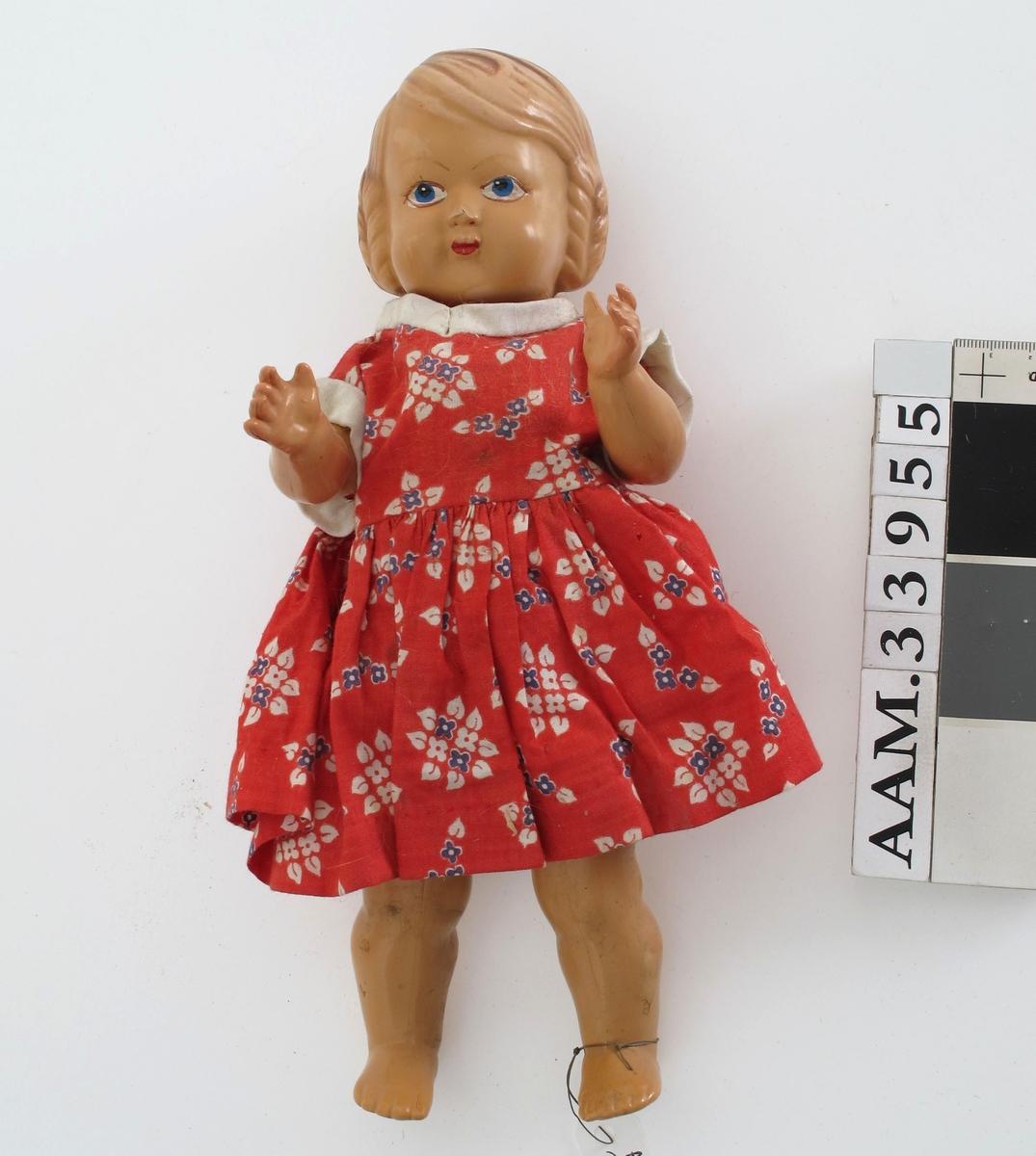 Dukke av støpte plastdeler. Hode og kropp i ett, mens armer og ben er støpt for seg og montert med strikk.   Hjemmesydde klær (?): Rød blomstret kjole. Underkjole. Underbukse i blå blomstet stoff.