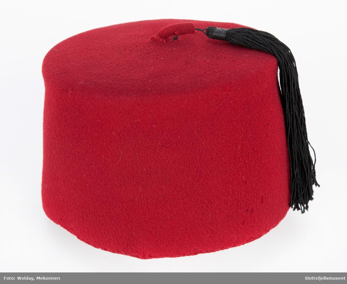Av rød filt med svart dusk. Grønn rosett ini toppen.
