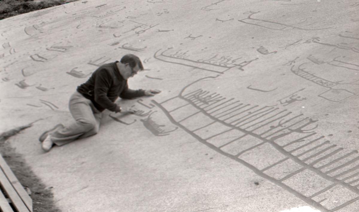 """En man som studerar hällristningar i Tanum. Hällristningsområdet i Tanum är ett område i Tanums kommun i Bohuslän där man funnit flera berghällar med stora mängder hällristningar från bronsåldern. Runt den största av dem, Vitlyckehällen, är Vitlycke museum uppbyggt. Hällen har närmare 300 inhuggna figurer och ca 170 skålgropar. Den kanske mest berömda scenen bland alla Tanums hällristningar, """"Brudparet"""", finns här. Bland de övriga närliggande hällarna märks Litsleby med en ca 2,3 meter lång spjutbeväpnad man, """"Spjutguden"""", och Aspeberget med en plöjningsscen, ett antal oxar och skepp. Hällen vid Fossum ligger en bit från de övriga. Den kännetecknas av en mer sammanhållen och konstnärlig komposition. Kanske är den gjord av en enda ristare.  Hällristningarna har i modern tid fyllts i med röd färg för att göra dem tydligare. Det är inte känt om de var målade från början.  (Hämtat från Wikipedia)"""