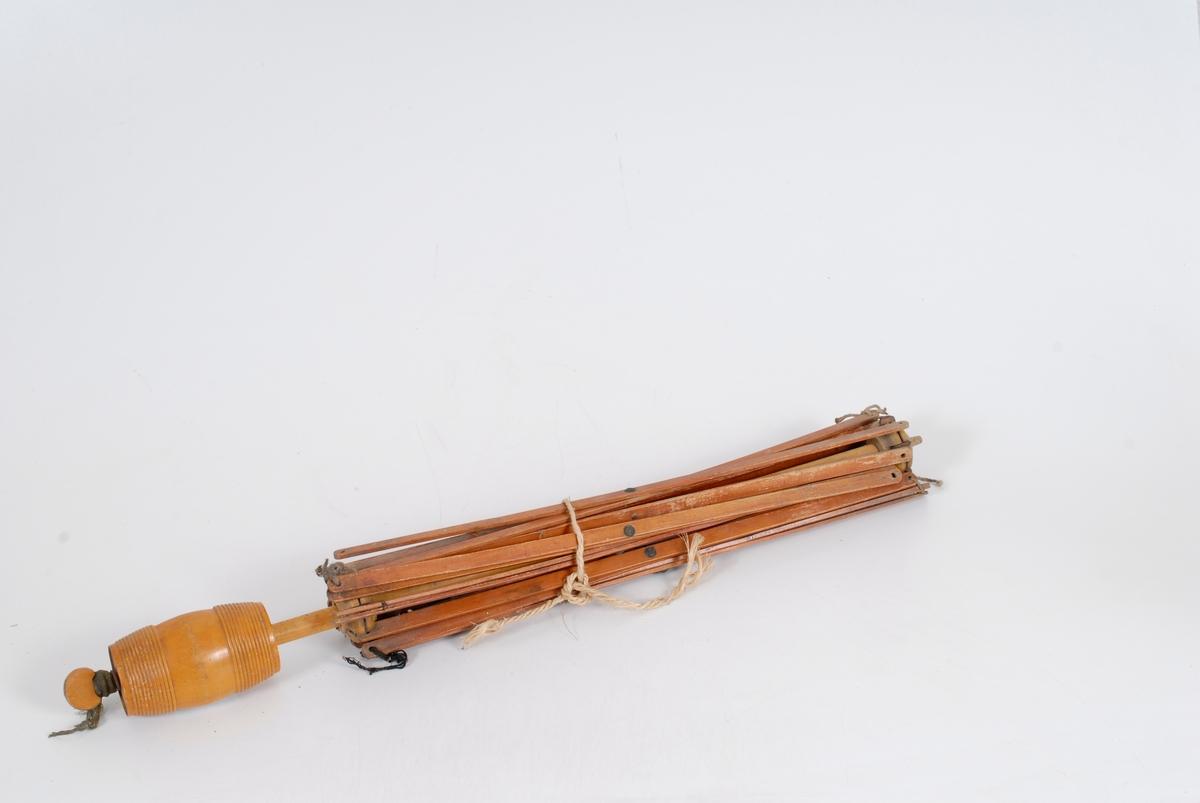 Form: Et sett med flate pinner, som henger sammen på midten og i endene og som krysser hverandre, er festet til en trering. Dette igjen er tredd på en rund trepinne. I enden på pinnen er det en stor skrustikke som hele stativet kan festes til en bordplate med.
