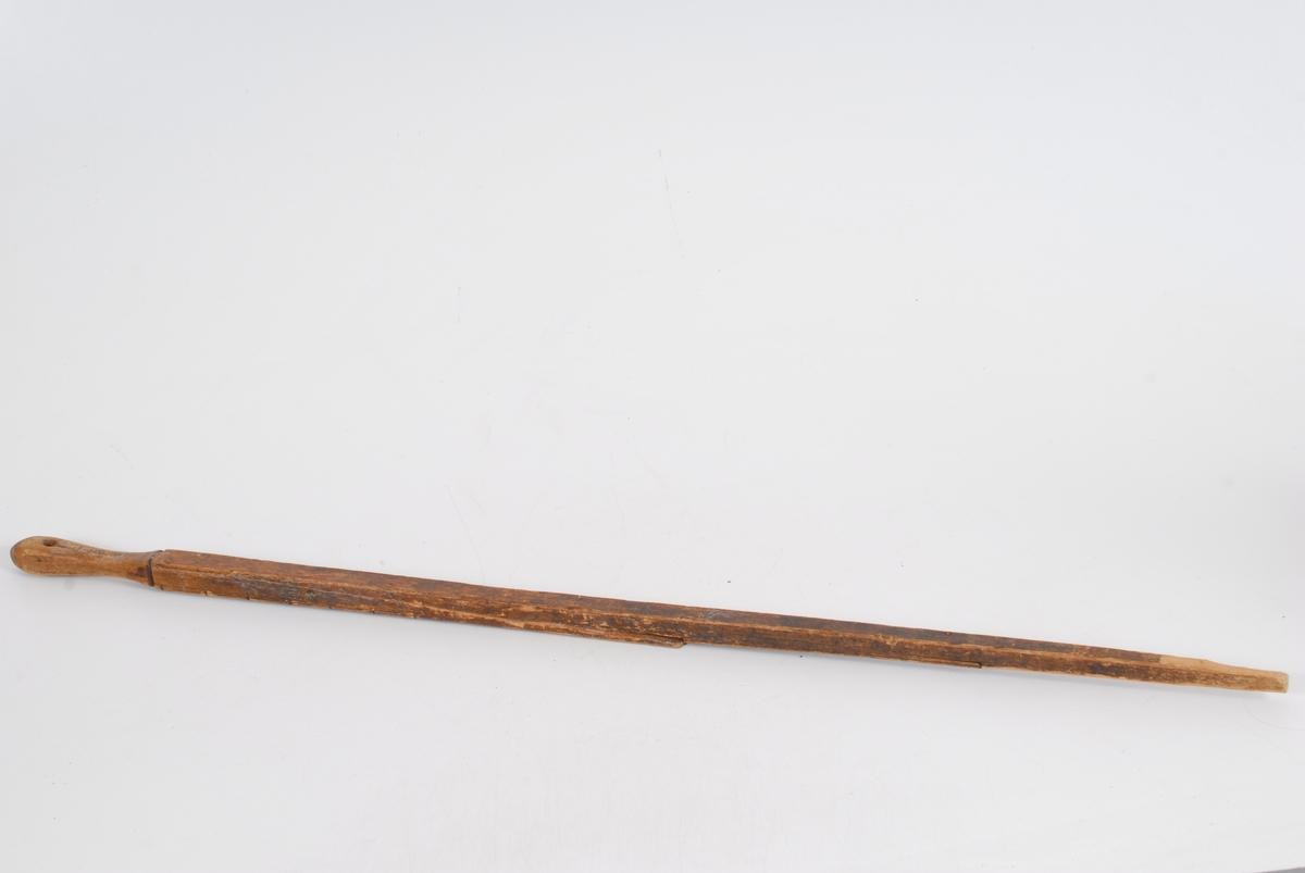 Form: Lang firkantet stokk som blir smalere mot ene enden og som har et dreid håndtak i andre enden.