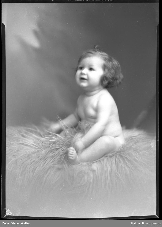 Ateljéfoto. Baby sittande på fårskinnsfäll.