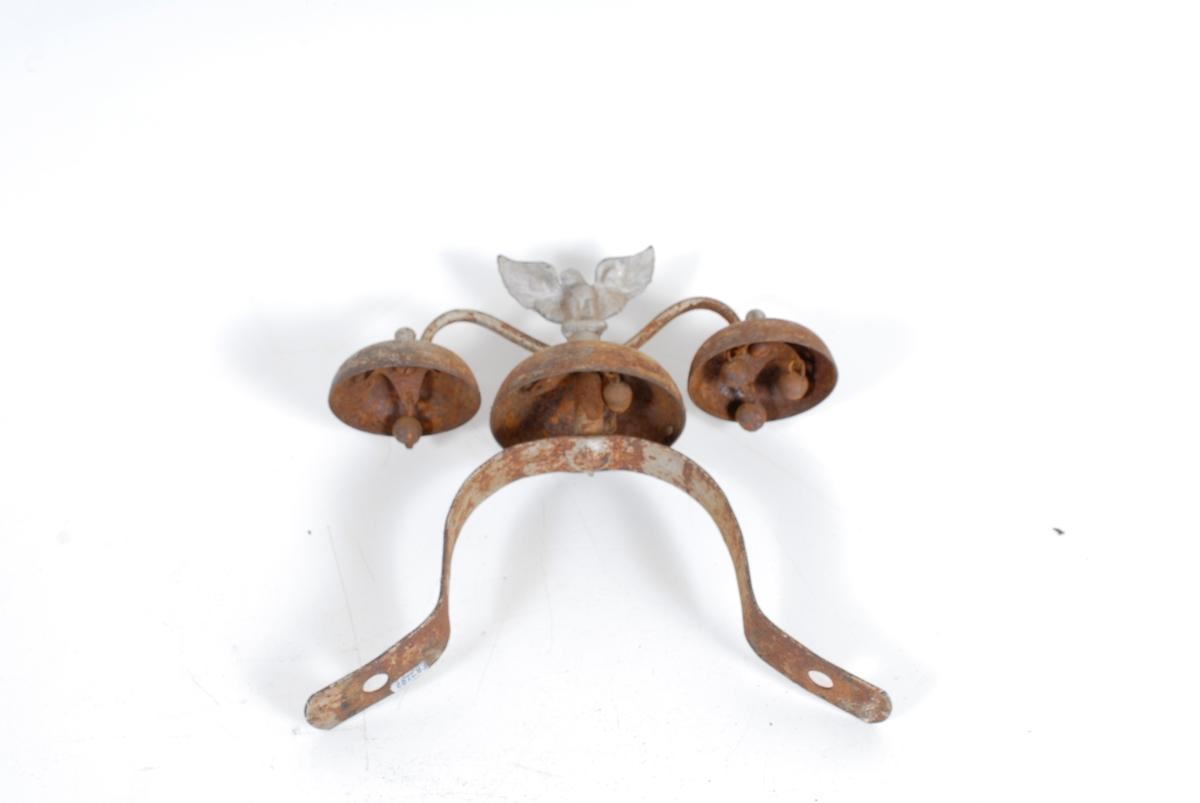 Form: På toppen: 3 dombj.festet t. en bøyle fra den store. Bj. har hatt trekuleform. hammere. En har alle, en har to og en har en igjen. På toppen av bj. i midt. er festet støpt ørn, utsl. vinger, hode mot v.