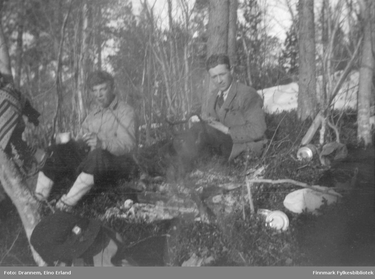 To menn sitter ved et lite bål i skogen. Sted og personer er ukjent.