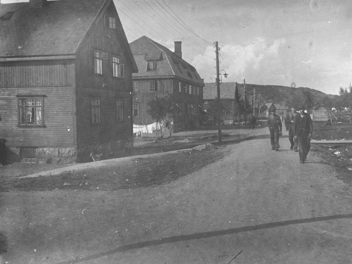 Gruvene i Bjørnevatn fotografert i sommerhalvåret. Tre menn i arbedsklær går langs en grusvei. Arbeiderboliger, hvitvask hengt til tørking mellom husene.