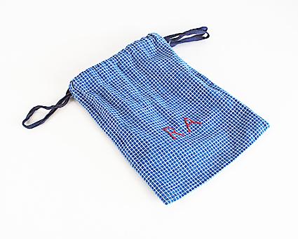 Kulpåse. Handsydd av blåvitrutig bomullslärft med dragsko och blå bomullsband, märkt med röda efterstygn: R A. Har innehållit metalldank (UM26382b).