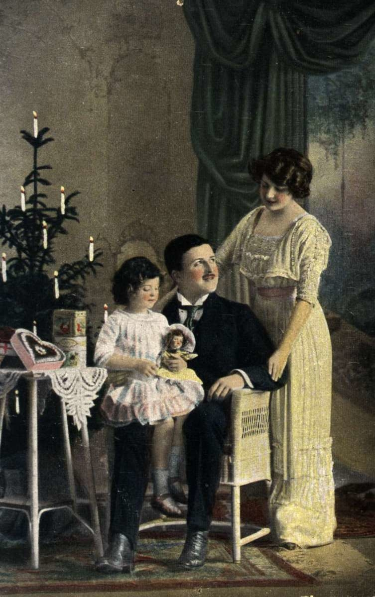 Julekort. Jule- og nyttårshilsen. Kolorert fotografi. Mor, far og datter ved juletreet. Datteren med dukke. Julegaver. Datert 1919.