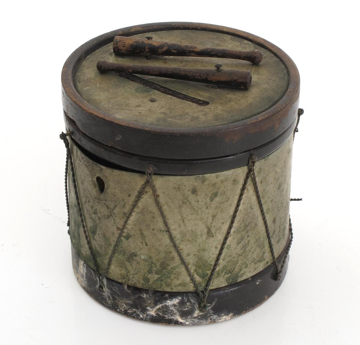 Sparebøsse i form av en liten tromme. Tre, sortmalt og messing. Sylinderformet tromme, trebunn, metallbånd om korpus med hyssing i siksak som på en tromme, messing topplate med sortmalt  trering om. Åpen spalte på toppen og to fastspikrede trommestikker.