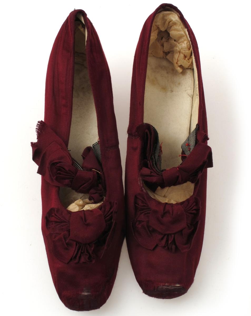 Sko til kjole AAM.4071. Av silke, skinn, lær. Smale sko i burgunder silke . med sløyfe foran og en sløyfe over vristen sydd på et sort og hvitstripet strikk. Foret med  hvitt skinn. Sterkt innsvunget hel, tynn lærsåle. Under begge  såler:  H.C.H. (innrisset). Inni er begge nummerert: 23817.