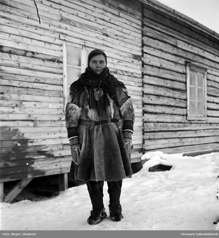 Ellen Johnsdatter Utsi kledd i samisk pesk med samisk belte, lue, sjal og votter. Fotografert av Elisabeth Meyer, mulighens i perioden rundt påske 1940 i området Kautokeino.