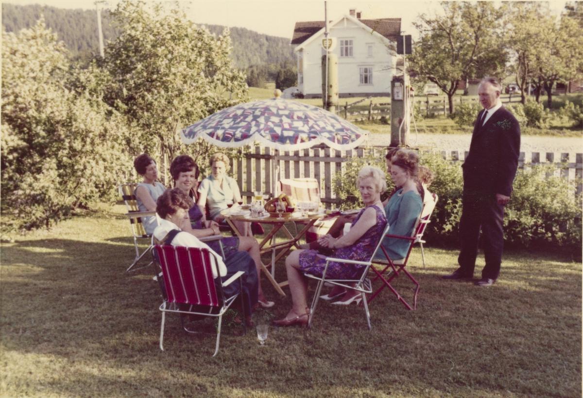 Selskap i hagen. I bakgrunnen ser vi Braate gård med to bensinpumper. Oppigarn ca. 1968