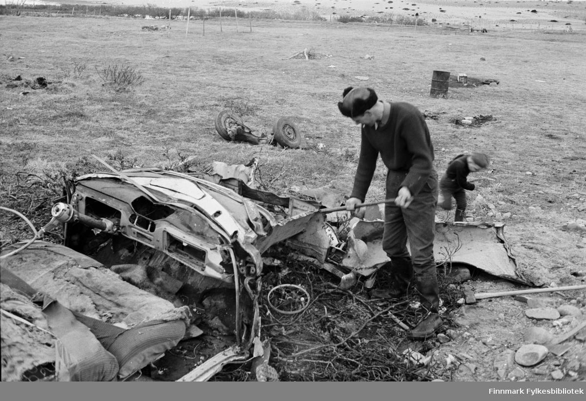 Serie med bilder fra Vadsø; trafikkulykker. Bilvrak. En person står ved bilvraket. Restene ser ut til å ligge på Vadsøya.