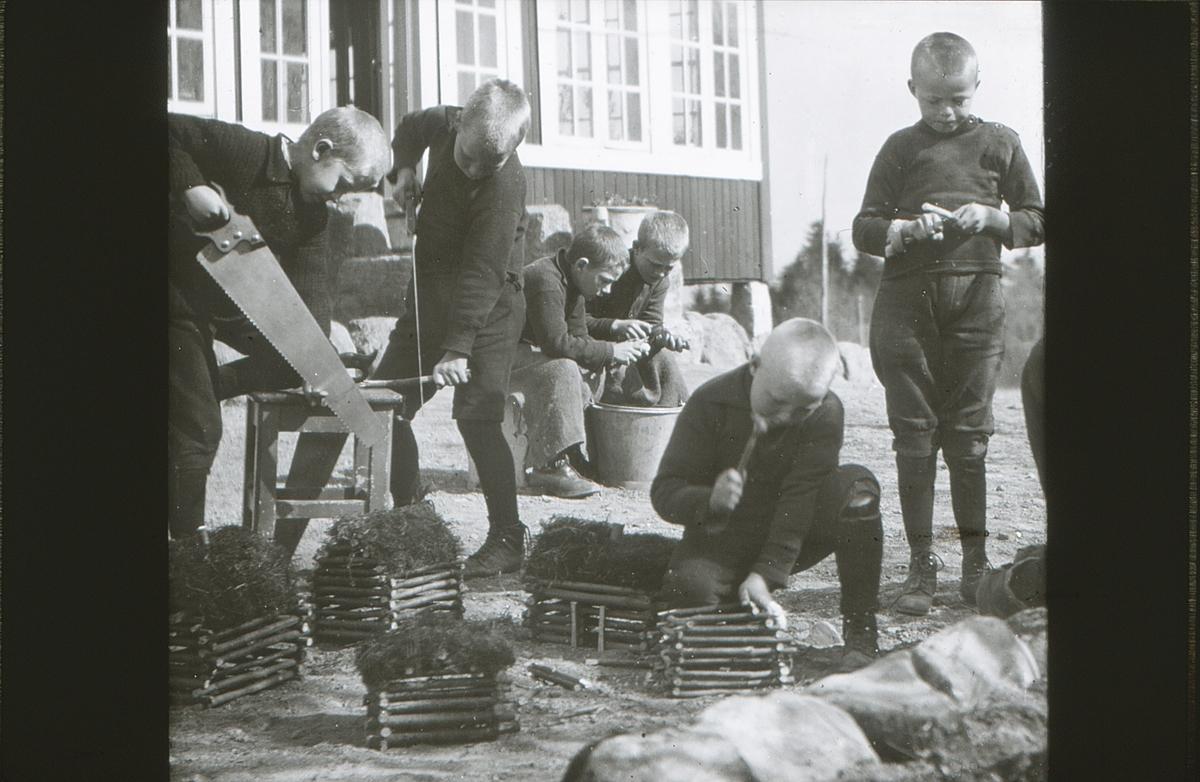 Gutter på friluftsskolen Vangen bygger en bondegård i miniatyr. To gutter sitter i bakgrunnen og skreller poteter.
