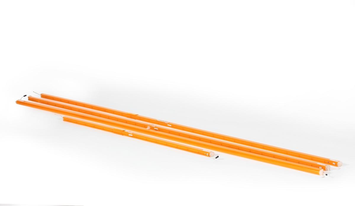 Oransje lysstoffrør, 4 stk., som er koblet sammen med små sammenkoblingsledninger. Lysstoffrørene har vært montert langs taket over bensinpumpene på bensinstasjonen