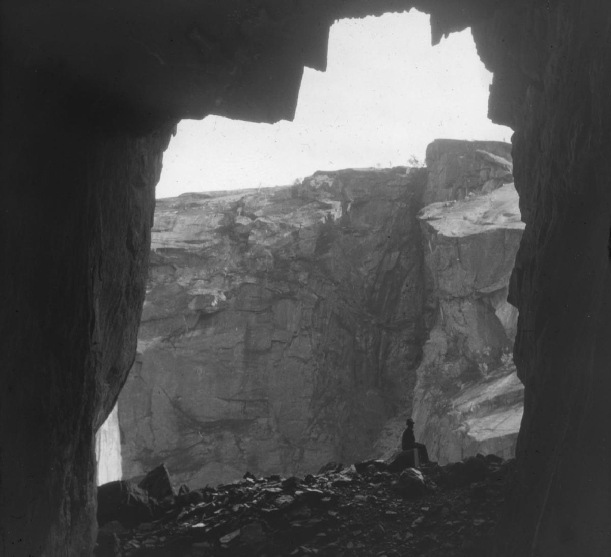 """""""N. 576b) Hule ved Hellemobotn, Tysfjord. R.10."""" står det på glassplaten. Bildet viser en hule i Hellemobotn, sett innenfra og ut. Hulen kalles """"Finngirkko"""" - noen tolker navnet som om det opprinnelig var Finngierkke - som betyr Finnsteinen. Like ovenfor denne hula ligger Bassoalgge som betyr Helligaksla. Vi er inne i et område med hellige navn. Vannet ved Finngirkko heter Sájvvajávrre som i følge sagnet har dobbel bunn.   En mann med mørke klær og hatt sitter utenfor hulen og viser dimensjonene i bildet. Hellmobotn (lulesamisk: Vuodnabahta)[1] ligger i Tysfjord kommune. Med 6,3 km i luftlinje mellom havet og grensen til Sverige er det her Norge er på sitt smaleste sør for Finnmark. Hellmofjorden er omgitt av høye fjell på alle kanter. Hellmofjorden er en fortsettelse av Tysfjorden, som igjen er en sidefjord til Vestfjorden. En del av Atlanterhavet når med det her helt inn til den skandinaviske høyfjellskjeden Kjølen. Lulesamisk (Julevsámegiella) er et samisk språk som snakkes av totalt 2 000 lulesamer, 1 500 i Sverige og 500 i Norge.[1] Det snakkes langs Luleälven i Sverige, spesielt rundt Jokkmokk, og i Nordland i Norge, særlig i Tysfjord"""