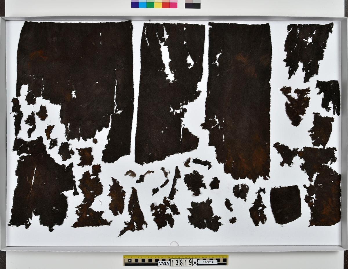 Textilfragment, byxa. 125 fragment uppdelade på fyndnummer 13819a-d. Fnr 13819a består av 44 fragment av ull vävt i tuskaft och valkat på ena sidan. En del av fragmenten har originalkanter med sömmar och fållar. Fnr 13819b består av 35 fragment av ull vävt i tuskaft. En del av fragmenten har originalkanter med sömmar. Fnr 13819c består av 40 fragment av ull vävt i tuskaft. En del av fragmenten har originalkanter med sömmar. Fragmenten är mycket sköra. Fnr 13819d består av 6 fragment mönstervävt band av ull.