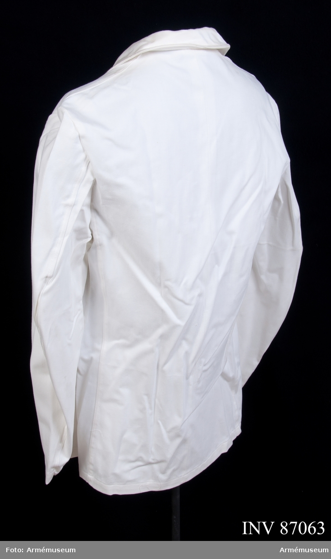 """Rock sydd i vitt bomullstyg, saknar knappar. Vidhängande etikett: """"Försvarets materielverk, Fastställs, M 7370-101000-4, Servitörsrock, 1985-09-18, (oläslig underskrift)"""". Storlek C 150. Etikett på insidan: """"Sanfor krympt, krammkläder, kramfors""""."""