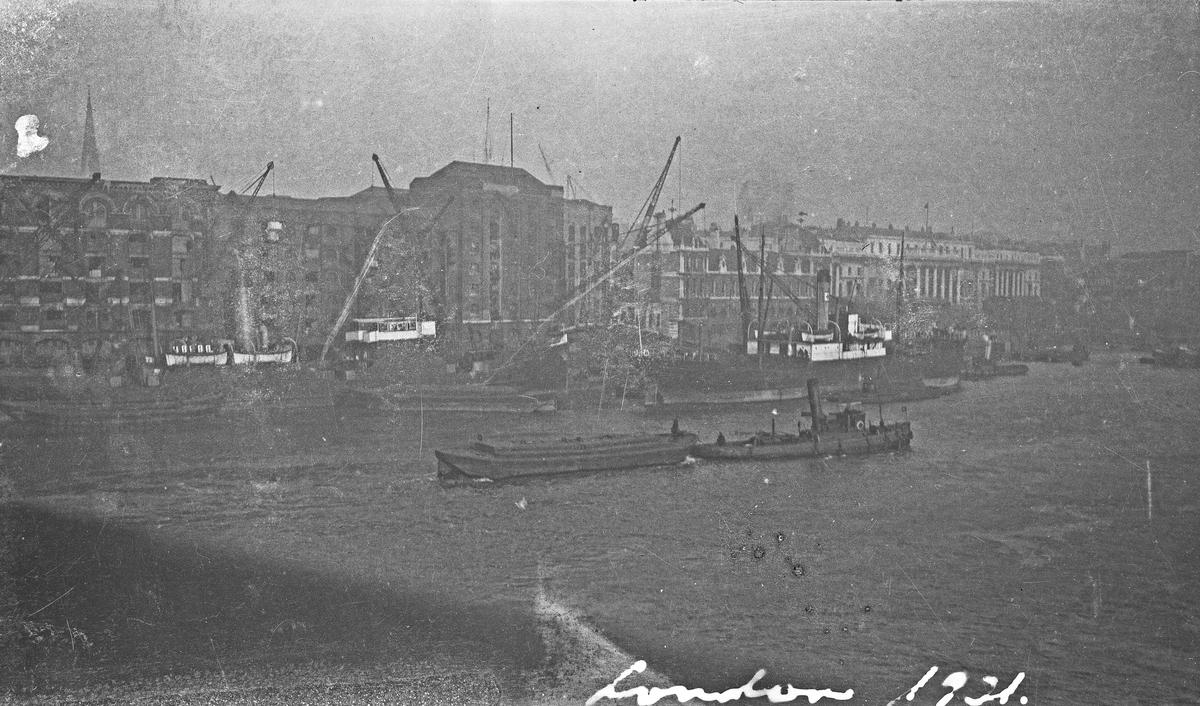 London havn. Flere skip ved kai. En taubåt med last på vei opp elven. Høye bygninger i bakgrunnen. Hverdagsfoto.