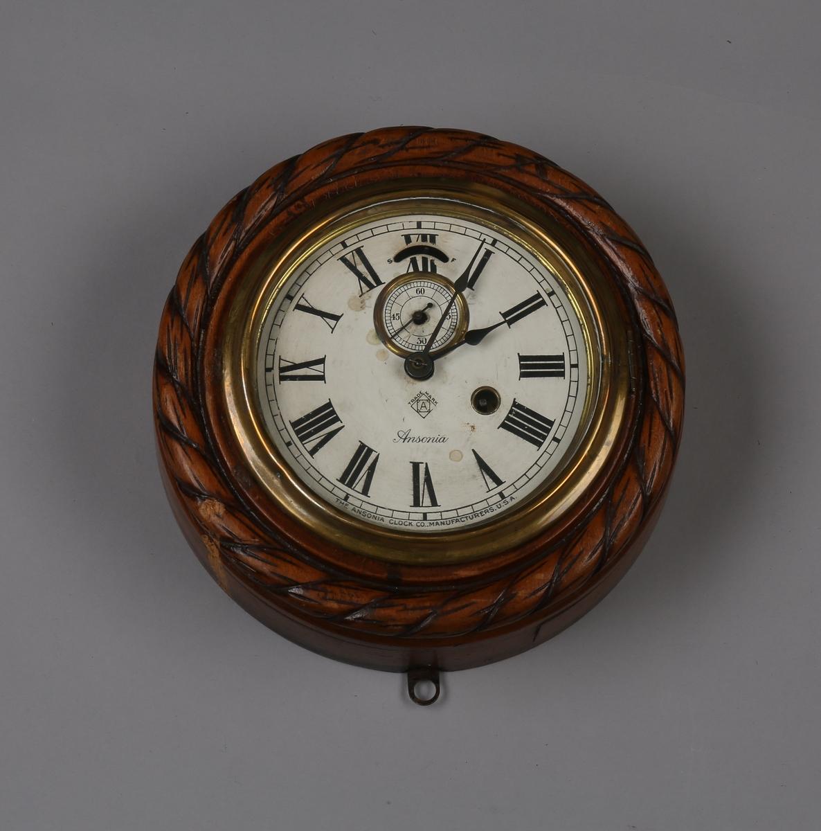 Rundt veggur fra salongen på DS NORDFJORD I, bg. 1915. Glass over urskive er hengslet fast og kan åpnes når klokken skal trekkes opp. Nøkkel til opptrekk mangler.