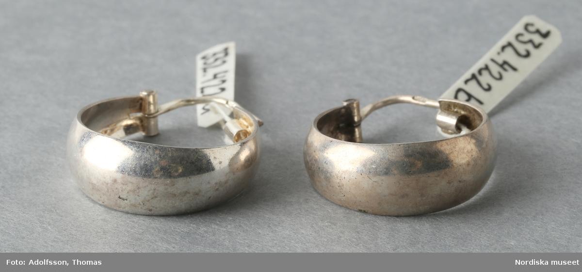 """Ett par örhängen, av silver. Breda ringar med låsanordning bestående av smal böjd ten, att fästa genom örat, upptill. Tenen stämplad """"925"""".  /Leif Wallin 2015-06-08"""