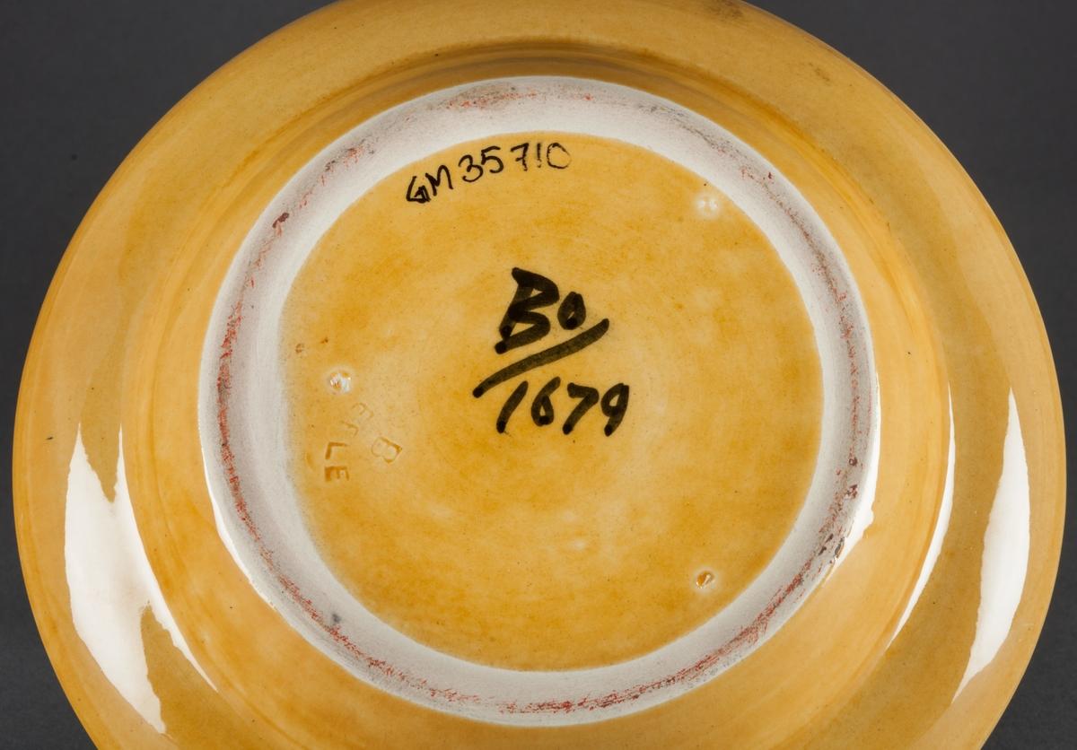 """Teservis bestående av 6 koppar med fat, sockerskål, gräddsnäcka, tekanna, två uppläggningsfat samt ett askfat. Delarna är tillverkade vid Bo Fajans i Gävle och formgiven av Allan Ebeling. Delarna har gul bottenglasyr med svart handmålad dekor. Kaffekopparna är av modell 1680, kaffekannan av modell 1676, sockerskål av modell 1677, gräddkanna modell 1678, uppläggningsfat modell 1679 (samtliga med kinesiserande dekor), askfat modell 1081 med cigarrökande herre som motiv och med text """"Havanna"""". Gåvan förmedlad av Dalarnas Museum 2002 som mottog den bland andra saker från en tesamlare i Falun."""