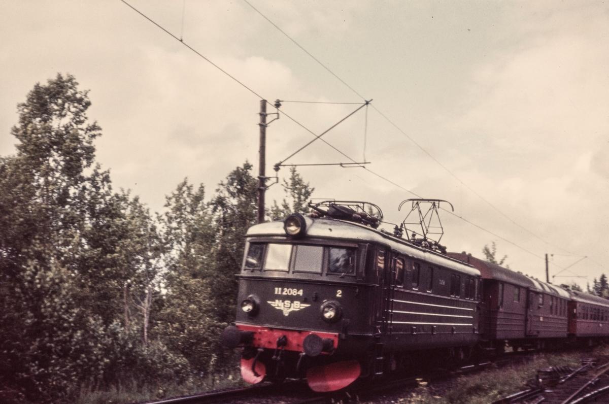 Ekspresstog fra Stockholm til Oslo Ø passerer ved Bingsfoss mellom Blaker og Sørumsand. Toget trekkes av elektrisk lokomotiv El 11 2084.