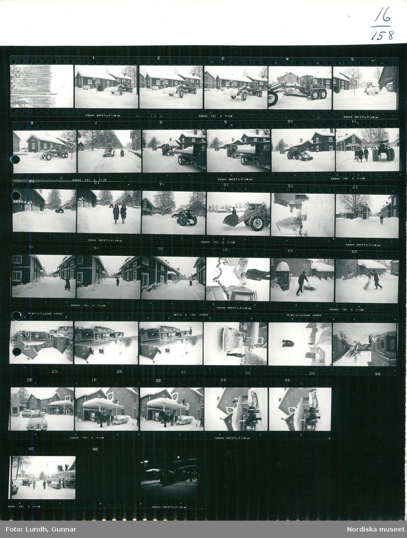 Motiv: (ingen anteckning) ; (Dagbok Julen i Leksand, Dalarna. Claësons minne), landskapsvy med snötäckt skog, snötäckt gatuvy med hus och en snöplog som plogar gatan, en traktor med skopa lastar snö på en lastbil, en person står i en traktorskopa, två kvinnor går på en snötäckt gata, en cyklist, en man skottar snö med en snösläde, en hund i snöfall, en man skottar snö på en bensinmack, en häst med en släde står på en bensinmack, nattbild av perrongen på en järnvägsstation med ett tåg.