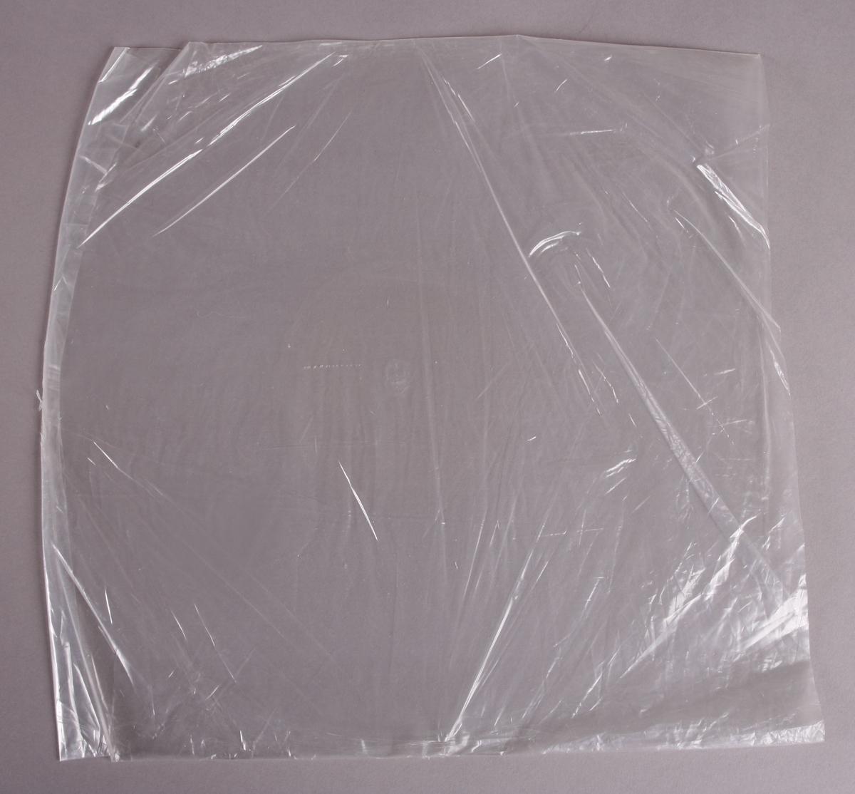 Grammofonplate i svart vinyl med plateomslag av papir. Platen ligger i en Plastlomme. Påskrift med blyant på baksiden av plateomslaget (se bilde).