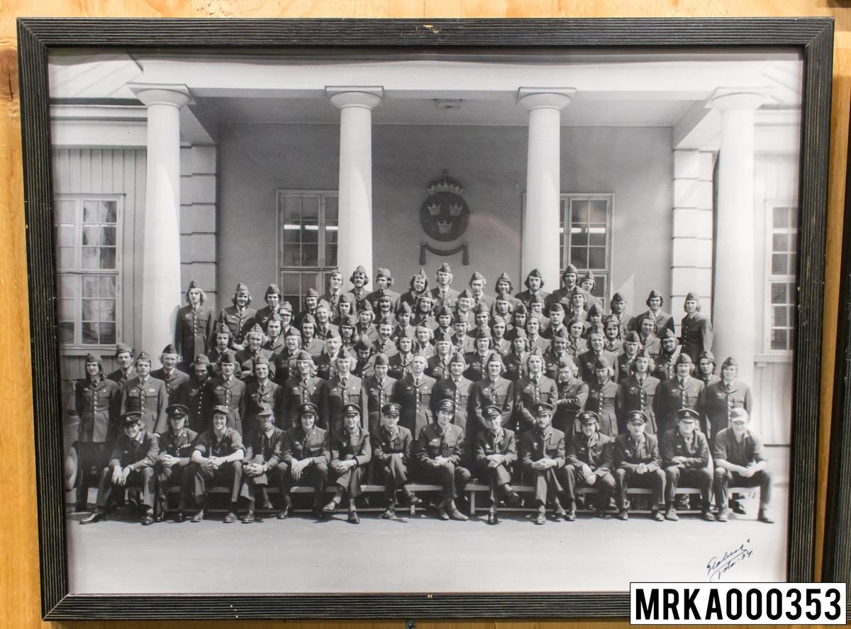 Fotografi taget på befäl och soldater som genomfört grundläggande soldatutbildning på 1:a Batteriet KA 2. Fotografiet taget utanför gymnastiksalen Gräsvik KA 2. Flobergs Foto 1974.