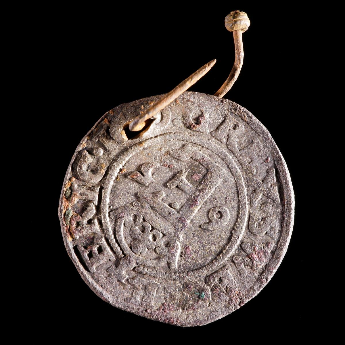 Mynt. 1/2 öre myntat av Erik XIV 1565. Hål med vidsittande knappnål av järn. Åtsida med krönt E och frånsida med Vasavapnet.