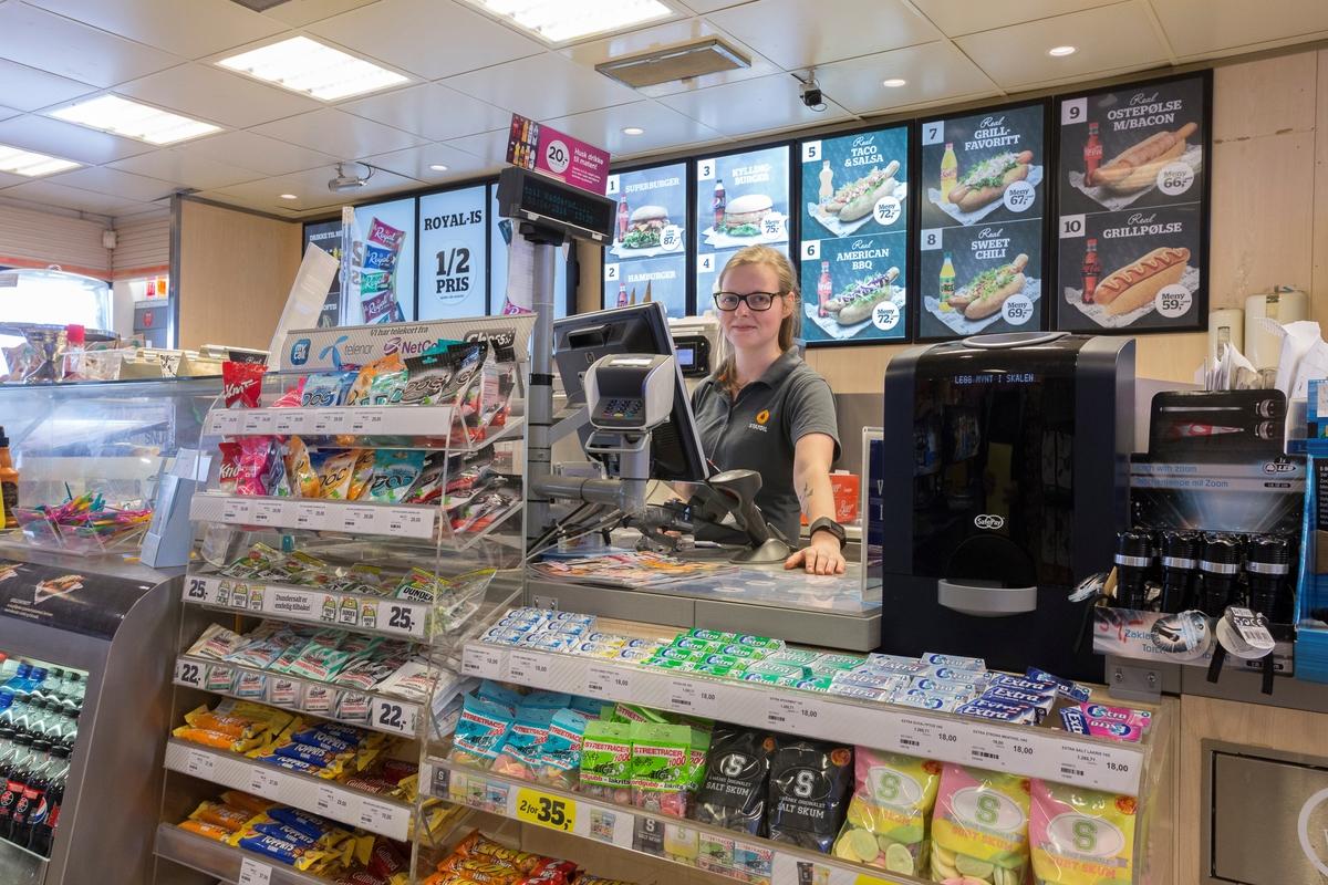 Statoil Nadderud. Butikkbetjening ved butikkdisk. Kortautomat og varer på  og rundt disken. Reklameskilt med varm mat i bakgrunnen.