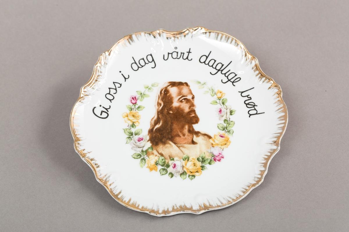 Tallerken i porselen. Emaljert hvit med blomsterdekor, Jesusbilde og tekst. Gull pyntekant. Har feste til vegg.