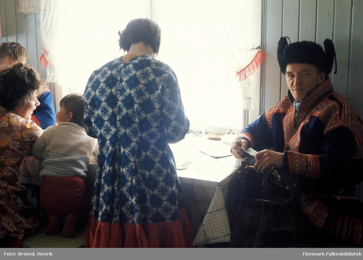 """Postfører Mathis Mathisen Buljo, bedre kjent som """"Post-Mathis"""" i samiske kretser, fotografert inne på kjøkkenet hos en av sine postkunder på postruta. Mathis til høyre i bildet med en pengeseddel i hånden. Kanskje er det en postanvisning som skal utbetales.  Fotograf Henrik Ørsteds bilder er tatt langs den 30 mil lange postruta som strakk seg fra Mieronjavre poståpneri til Náhpolsáiva, videre til Bavtajohka, innover til øvre Anárjohka nasjonalpark som grenser til Finland – og ruta dekket nærmere 30 reindriftsenheter. Ørsted fulgte «Post-Mathis», Mathis Mathisen Buljo som dekket et imponerende område med omtrent 30.000 dyr og reingjetere som stadig var ute i terrenget og i forflytning. Dette var landets lengste postrute og postlevering under krevende vær- og føreforhold var beregnet til 2 dager. Bildene gir et unikt innblikk i samisk reindriftskultur på 1970-tallet. Fotograf Henrik Ørsted har donert ca. 1800 negativer og lysbilder til Finnmark Fylkesbibliotek i 2010."""