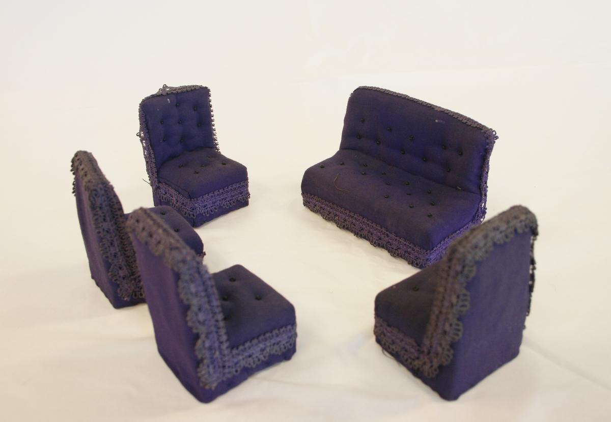 Dukkemøbler 5 stk.  A) Sofa, helt overtrukket i bomullsstoff med sorte perler som knapper på ryggdelen og setet. Påsydd broderikant langs hele sofaen. Uten armlener, rett høy rygg.  B-E) Stoler 4 stk. Helt overtrukket i bomulsstoff med sorte perler som kapper på ryggdelen og setet. Påsydd broderikant langs hele stolen, uten armlener med høy rett rygg.