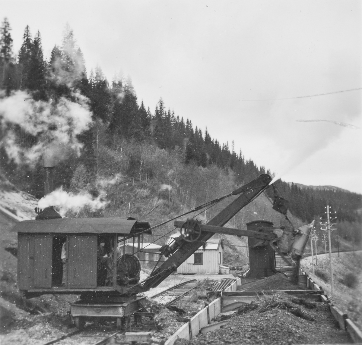 Opplasting av grus på jernbanevogner i Spølrem grustak mellom Laksfors og Eiterstraum stasjoner på Nordlandsbanen.  Det benyttes dampdrevet gravemaskin.