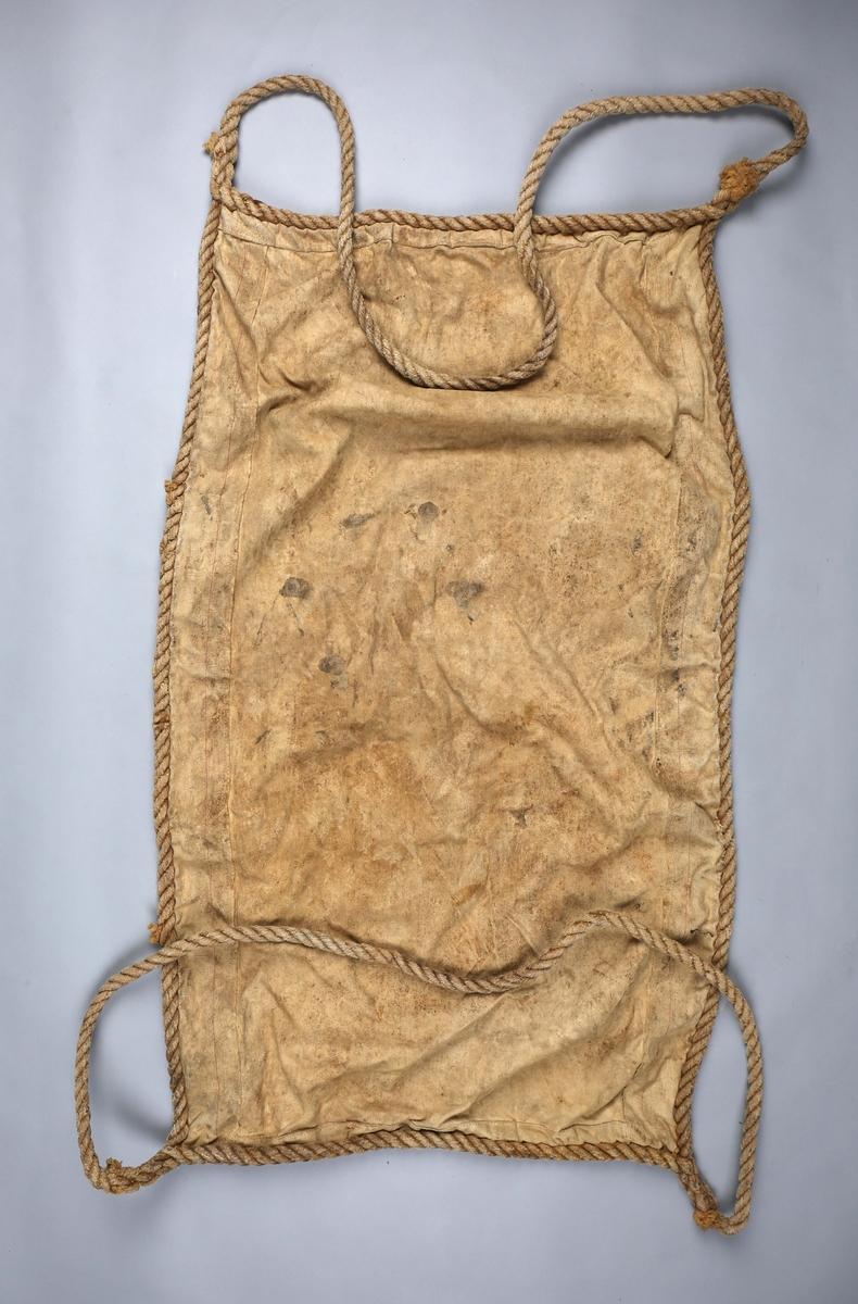 Løftesele i seilduk med hampetau. Brukt for lasting og lossing av hest/storfé ombord i fjordabåter. Rektangulær med stropper i hver kortende.
