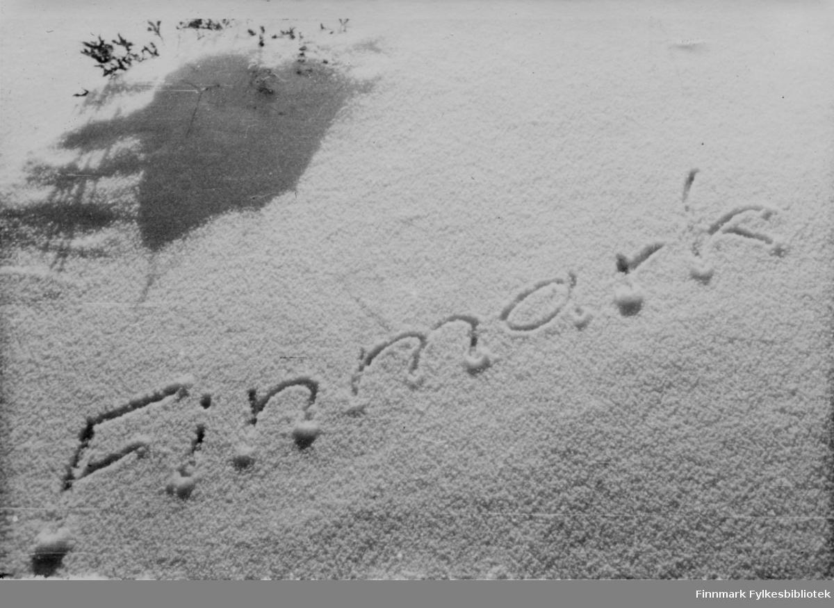 """En soldat har skrevet """"Finnmark"""" i snøen.   Bildeserien """"Frigjøringen av Finnmark 1944-45"""" viser et unikt materiale fotografert av soldater i Den Norske Brigade, 2. Bergkompani under deres oppdrag """"Frigjøringen av Finnmark"""" som kom i stand under dekknavn """"Øvelse Crofter"""". Fakta rundt dette bildematerialet illustrerer iflg. vår informant, George Bratli: """"2.Bergkompani, tilhørende Den Norske Brigade i Skottland,  reiste fra Skottland 30. oktober 1944 med krysseren «Berwick» til Scapa Flow på Orkenøyene for å slutte seg til en større konvoi som skulle være med til Norge. Om bord på andre skip var det mange russiske krigsfanger som hadde vært på tysk side og som nå ble sendt hjem.  2.Bergkompani forlot havn 1.november 1944 og kom til Murmansk, Sovjetunionen, 6. november 1944.  De ble her lastet om og fraktet til Petsamo, Sovjetunionen, hvor de ankommer 11.november 1944.  Kompaniet reiser så til Sandnes utenfor Kirkenes og blir forlagt der frem til 26.november 1944. De flytter så videre til Skipparggura.  Den 29.november reiser deler an kompaniet til Rustefielbma og Smalfjord og noen drar opp på Ifjordfjellet.   17. desember ankommer resten av kompaniet til Smalfjord. 30.desember blir en avdeling sendt til Hopseide og 8. januar 1945 blir noen sendt til Kunes. Den 14. januar er kompaniet delt og ligger i Kunes, Kjæs, Børselv, Hopseide og Smalfjord. 5. februar 1945 blir 3.tropp sendt over Porsangerfjorden for å operere i Olderfjorden. Her var de i kamp og hadde tap i  Billefjord og Sortvik. 8.mars 1945 kom noen til Renøy og 12. mars kom første del av kompaniet til Brennelv. 7.mai begynte kompaniet å bygge ny kai i Hambukt. 19. mai ble de som hadde falt begravd i Lakselv. 8. juni ble kompaniet flyttet fra Brennelv til Tromsø for så å bli sendt videre til Mo I Rana 16.juni."""""""