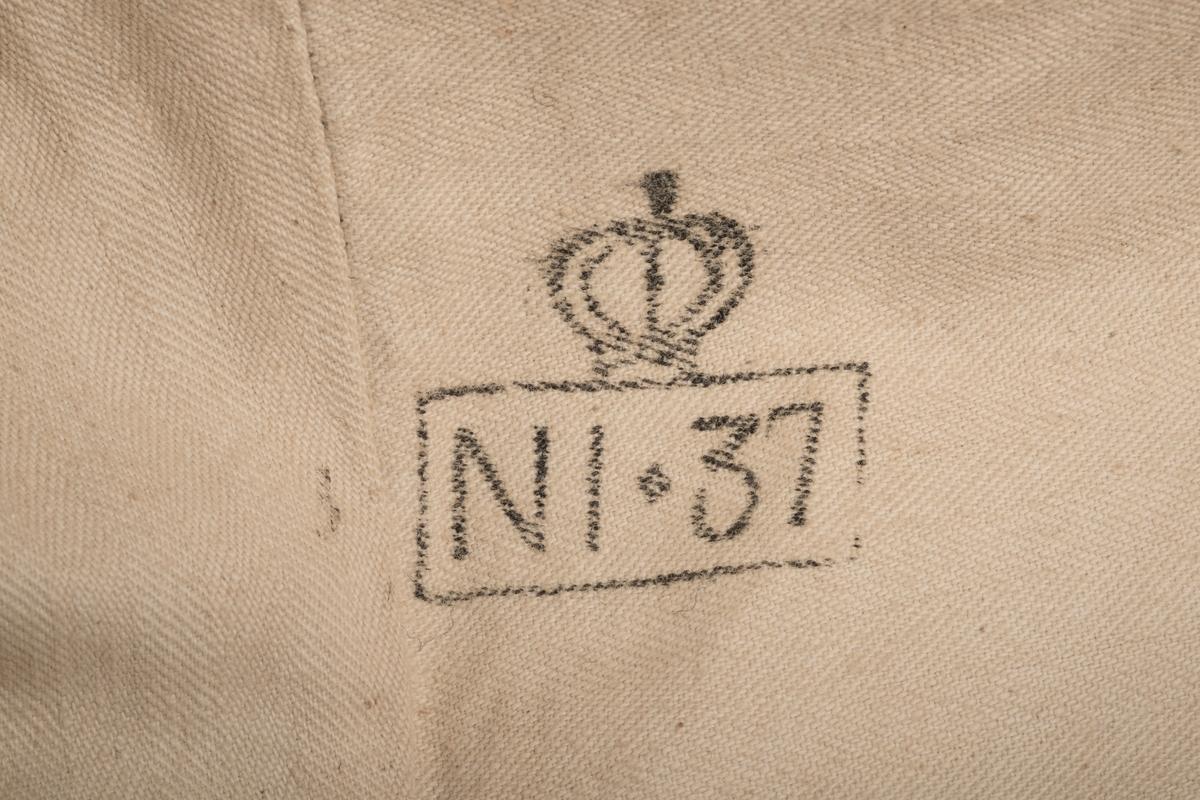 """Deler av fangedrakt fra Grini. Jakke og lue fra en gammel gardeuniform i mørkeblå ull. Fôret i naturhvit lin på kroppen og i lua, og lysegrå lin i ermene, samt et sett med ekstra knapper.  På høyre bryst er det sydd fast to merker. Det øverste er fangenummeret """"8684"""" som identifiserer brukeren som Haakon Rygh. Under denne sitter et merke """"J"""" som identifiserer han som en """"jugendfange"""", altså en ungdomsfange.  Uniformjakken har tilsammen 12 tinnknapper med den norske riksløven på, 8 stk. skjult under stolpen, en i hver erme, og to i korsryggen.  På innsiden av jakken er det to stempler. En i nakken """"Garden"""" og en under venstre bryst """"NI 37"""".  På skulderne er det små rester av rød stoff."""