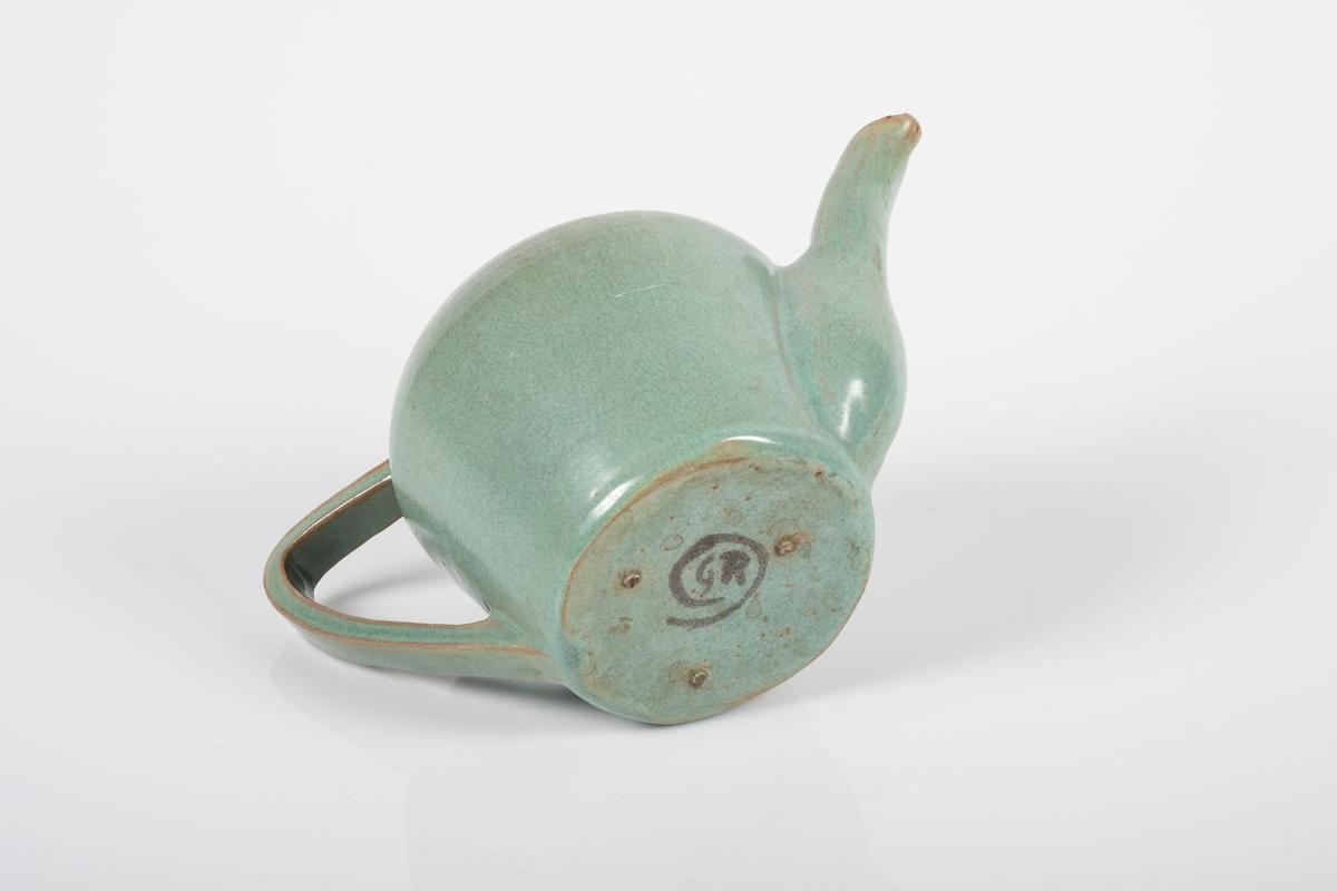 Tekanne i keramikk med grønn lasur. Har tut og buet hank. Grinisymbolet på bunnen av tekannen. Tre små knotter på undersiden av kannen, usikker funksjon.