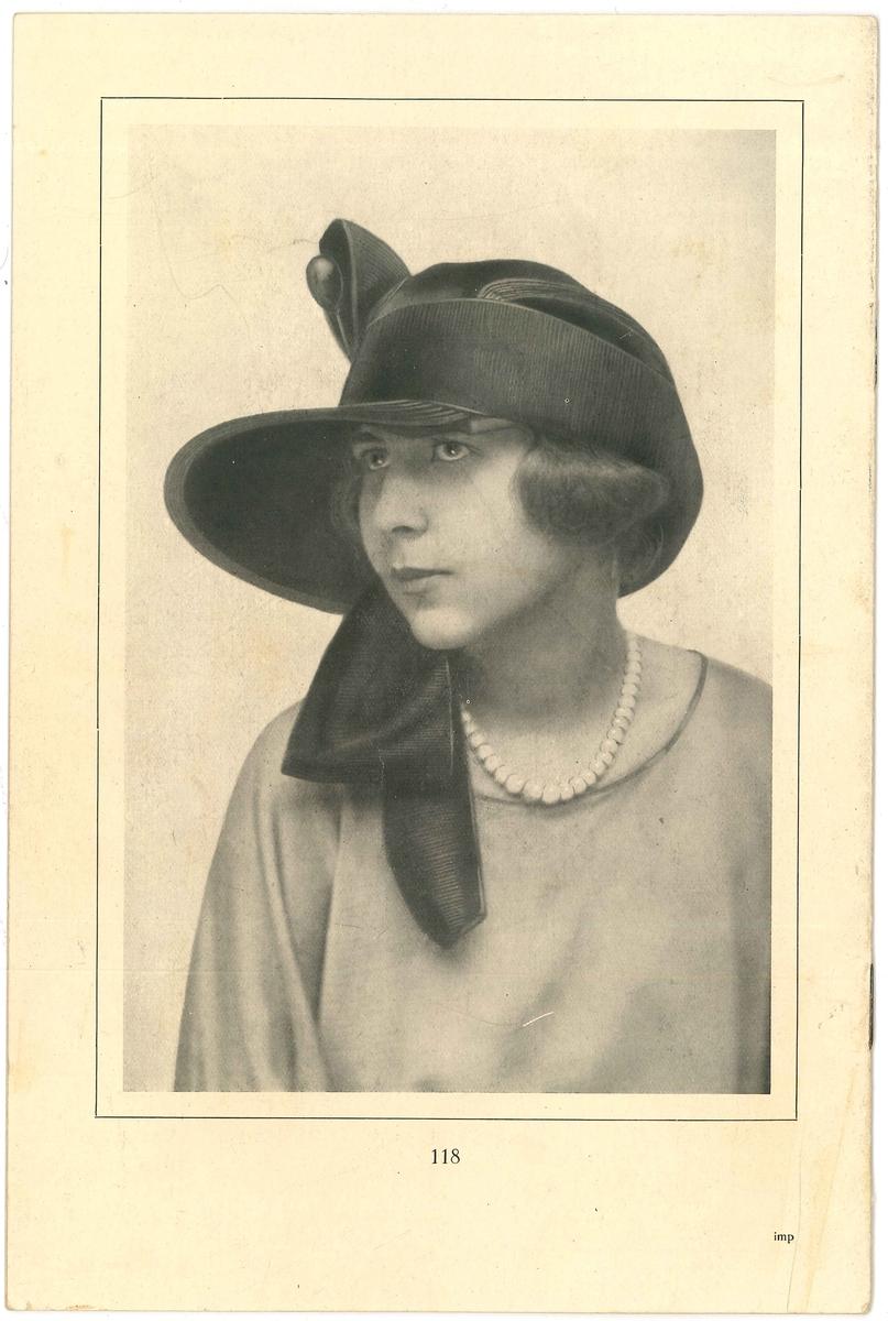 Baksida på modehäfte med en kvinna i hatt.   Modeller på hattar. Från år 1923. Modejournalen fanns i Amanda Nordahls Modeaffär, Vänersborg.