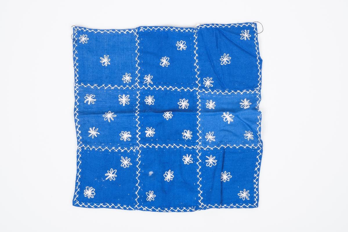 Nesten kvadraktisk kongeblått tøystykke med broderte små hvite blomster med 8 blomsterblader på. Brukt som vognteppe til dukkevogn. Satt sammen av 9 mer eller mindre kvadratiske tøybiter, sydd sammen med heksesting. Blomstene er gruppert i grupper på tre eller fem blomster per tøybit.
