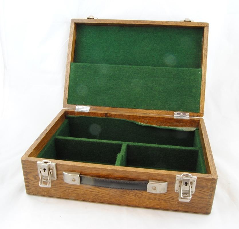 """Verktygsväska av brunbetsad ek med sinkade hörn. Lock och botten är av plywood. Väskan har infällda gångjärn till locket. På motstående sida sitter ett bärhandtag av läder och två förnicklade lås tillverkade av """"CHENEY ENGLAND"""". Invändigt är lock och botten klädda med grön filt. På insidan av locket finns ett fack för en tillhörande inventarielista. Väskan har tre fack för verktyg, ett avlångt och två kortare. Verktygsväskan har en tillhörande låda (:2) att ställa ovanpå facken. I inventarielistan är de angivna """"TA 1200: 1 st låda + 2 st nycklar"""". Nycklarna saknas."""