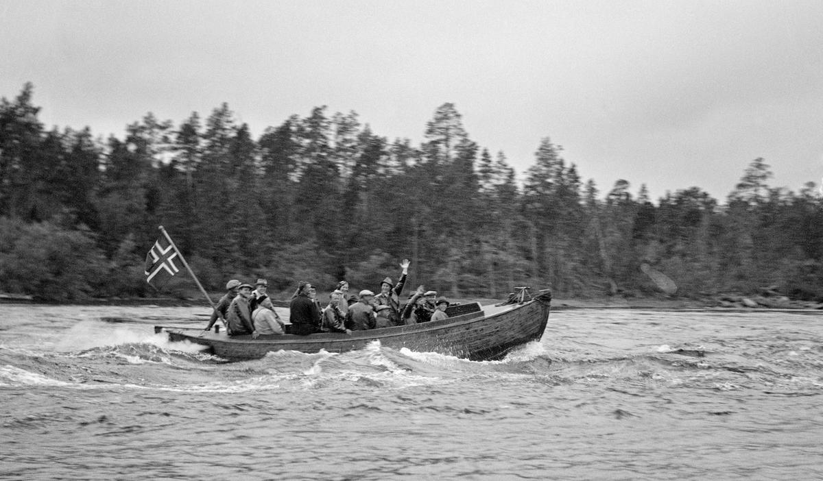 Deltakere under utferden som ble arrangert i forbindelse med Nord-Norges skogmannsforbunds 25-årsjubileum i motorsnekke på Pasvikelva.  Under båtturen fra Nesheim til Kobbefoss passerte de blant annet Ulvestryket, hvor dette fotografiet er tatt.  Det satt cirka 25 personer om bord i båten, de fleste menn.  To av dem vinket mot fotografen.  Båten førte norsk flagg.