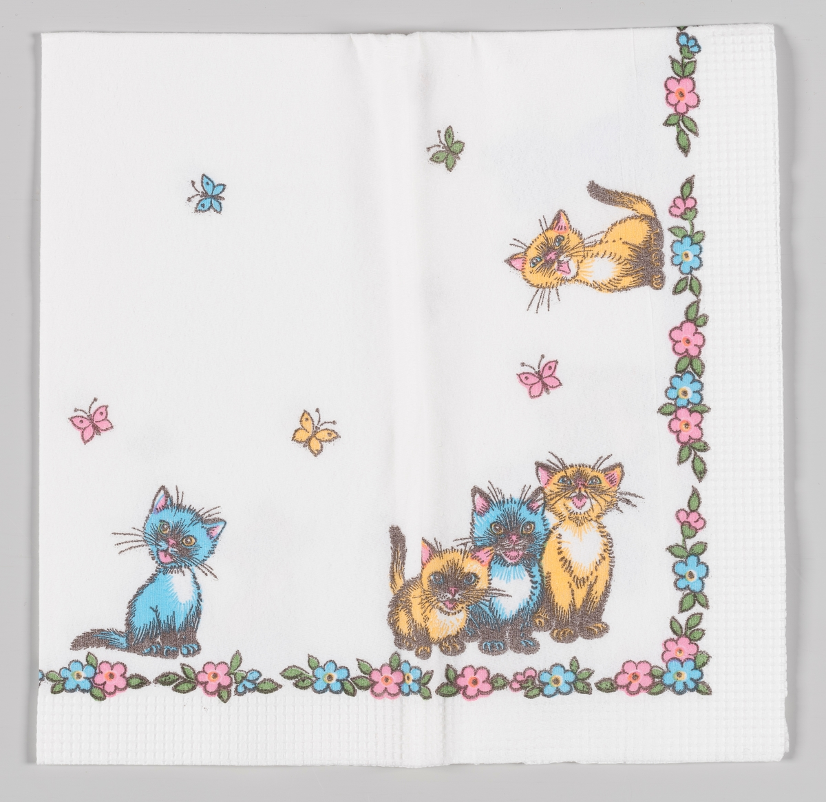 Fem katter i fargene gul og blå sitter langs en kant av blomster mellom flygende sommerfugler.