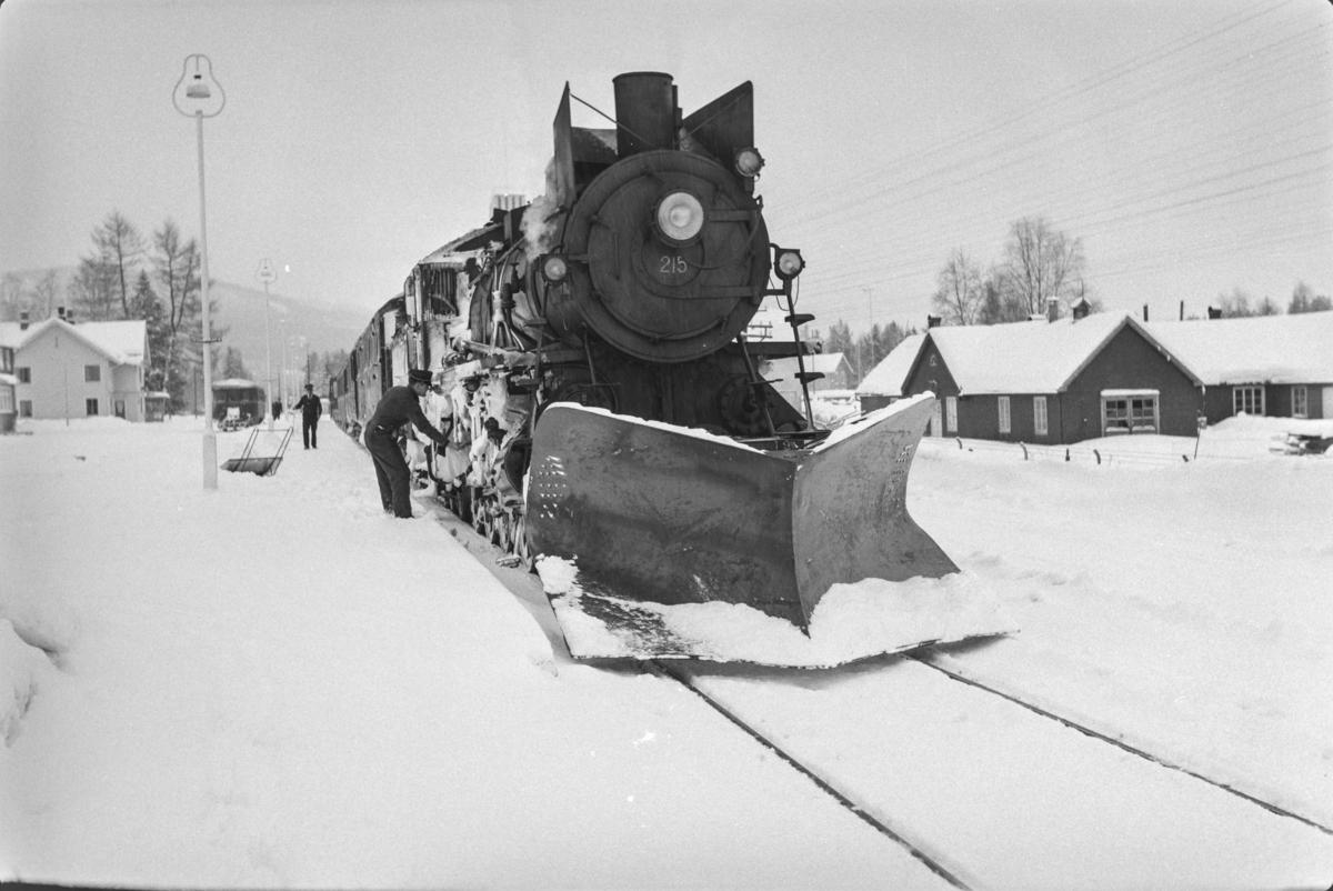 Persontog fra Oslo Ø til Trondheim over Røros, Pt. 301, på Koppang stasjon. Toget trekkes av damplokomotiv type 26a nr. 215.