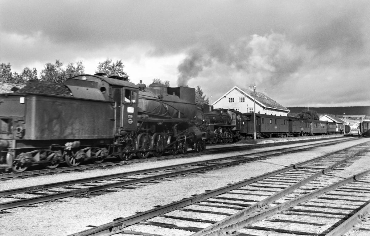 Kryssing på Røros stasjon mellom dagtoget fra Oslo Ø til Trondheim, tog 301 og godstog fra Trondheim til Hamar, tog 5716. Tog 301 trekkes av damplokomotiv type 26c nr. 413, godstoget trekkes av damplokomotiv type 26b nr. 230.