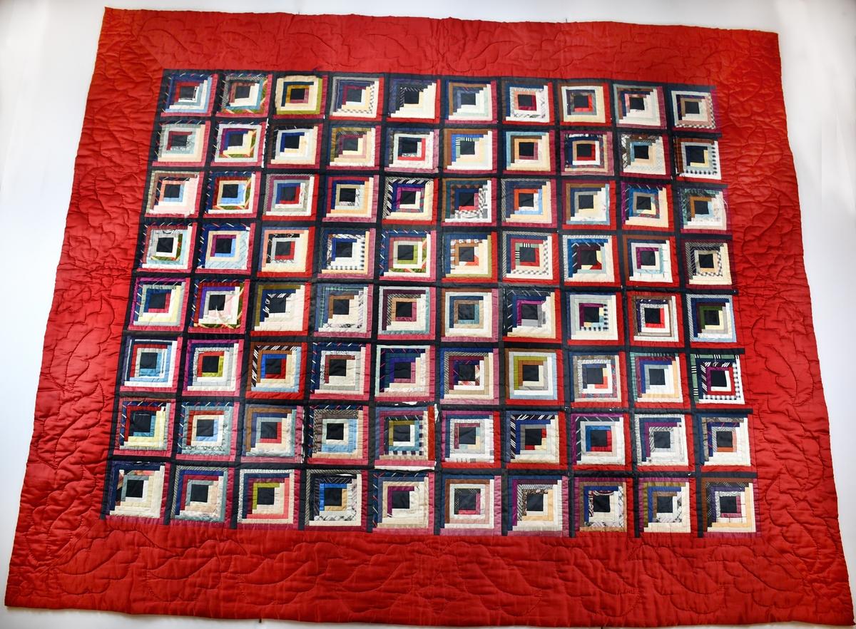 Anmärkningar: Lapptäcke, handsytt av kravattsiden och annat siden. Täcket är kantat med ca 20 cm bred bård av rött siden, bården har bladformiga mönsterstickningar. Täcket fodrat med grått bomullstyg och stoppat med vadd. Täcket är sytt av ca 1 cm breda remsor sammanfogade till kvadrater 13,5 x 13,5 cm diagonalt indelade i en mörk och en ljus halva. Kvadraterna vars mörka hörn alla är satta åt samma håll, är sammanfogade av svarta band. Täcket sytt av säljarens farmors mor, (farmodern gift 1881). Köpt tillsammans med täcken invnr 22933 och 22934 för 100:-. Den röda bården renoverad. Något trasigt sidentyg.