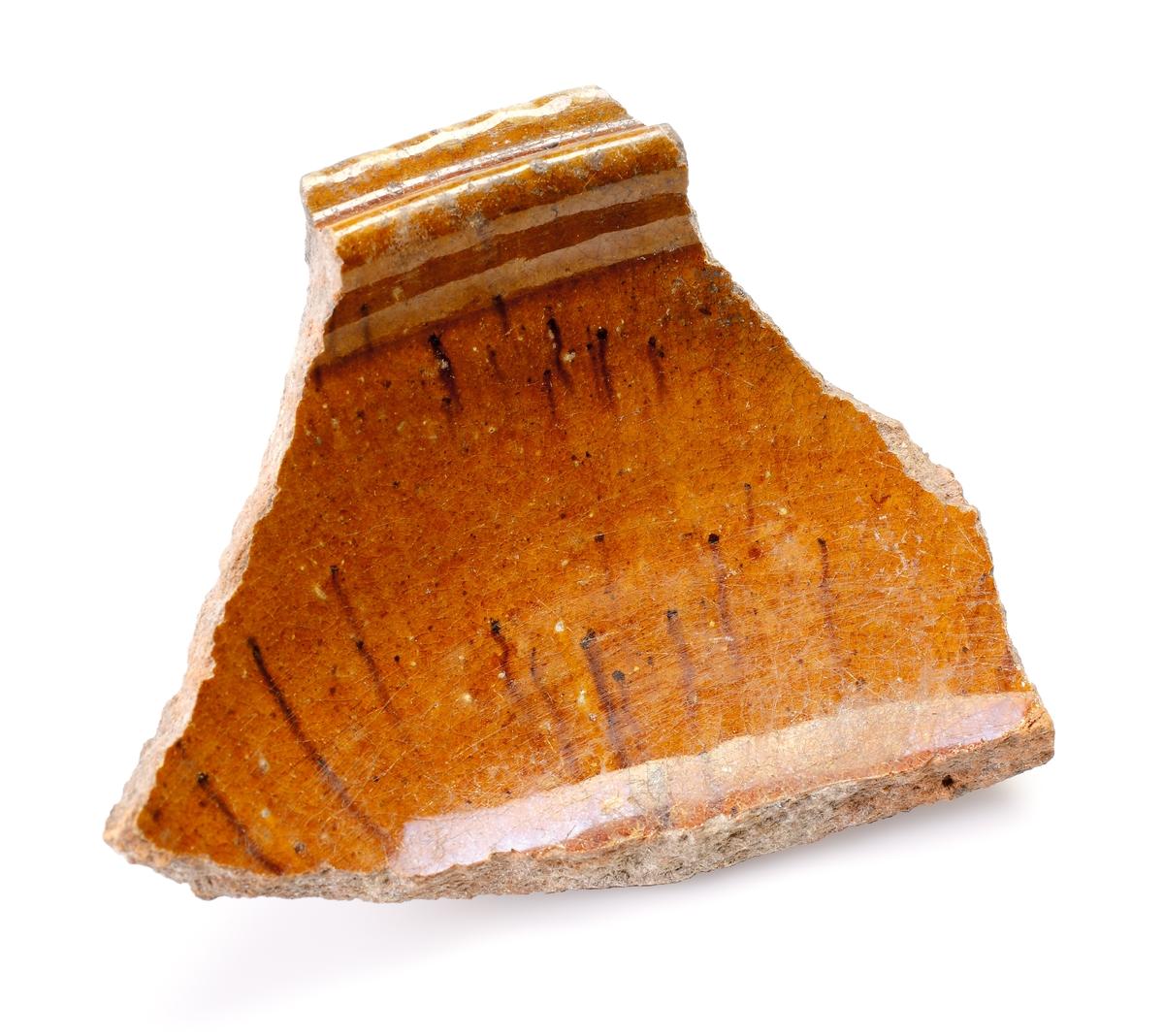 Buk- samt del av mynningsfragment med vertikal hank. Invändig brun glasyr med mörkbruna inslag. av yngre rödgods. Utvändig brun glasyr med dekor och prickmönster av piplera på bukdel och mynningskant. Prickmönster av piplera även på hank och vulster. Möjligen en kruka eller ett liknande hushållskärl. Passar ihop med M 17000-2282 och torligen även med 2304 och 2333. Tillverkad i västra Tyskland år 1550 - 1650.
