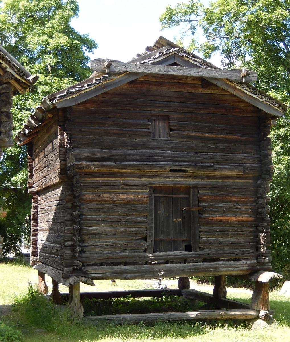 Det högra av de två timrade härbrena på Delsbogården är uppfört i två våningar, med utkragande övervåning, stående på stolpar och syllvarv. Taket är ett sadeltak, med tätskikt av näver samt takved. Byggnaden är troligen uppförd under 1700-talet.   Härbret kommer från Tjärnmyra by, Delsbo socken i Hälsingland. Det uppfördes på Skansen under åren 1939-1940.